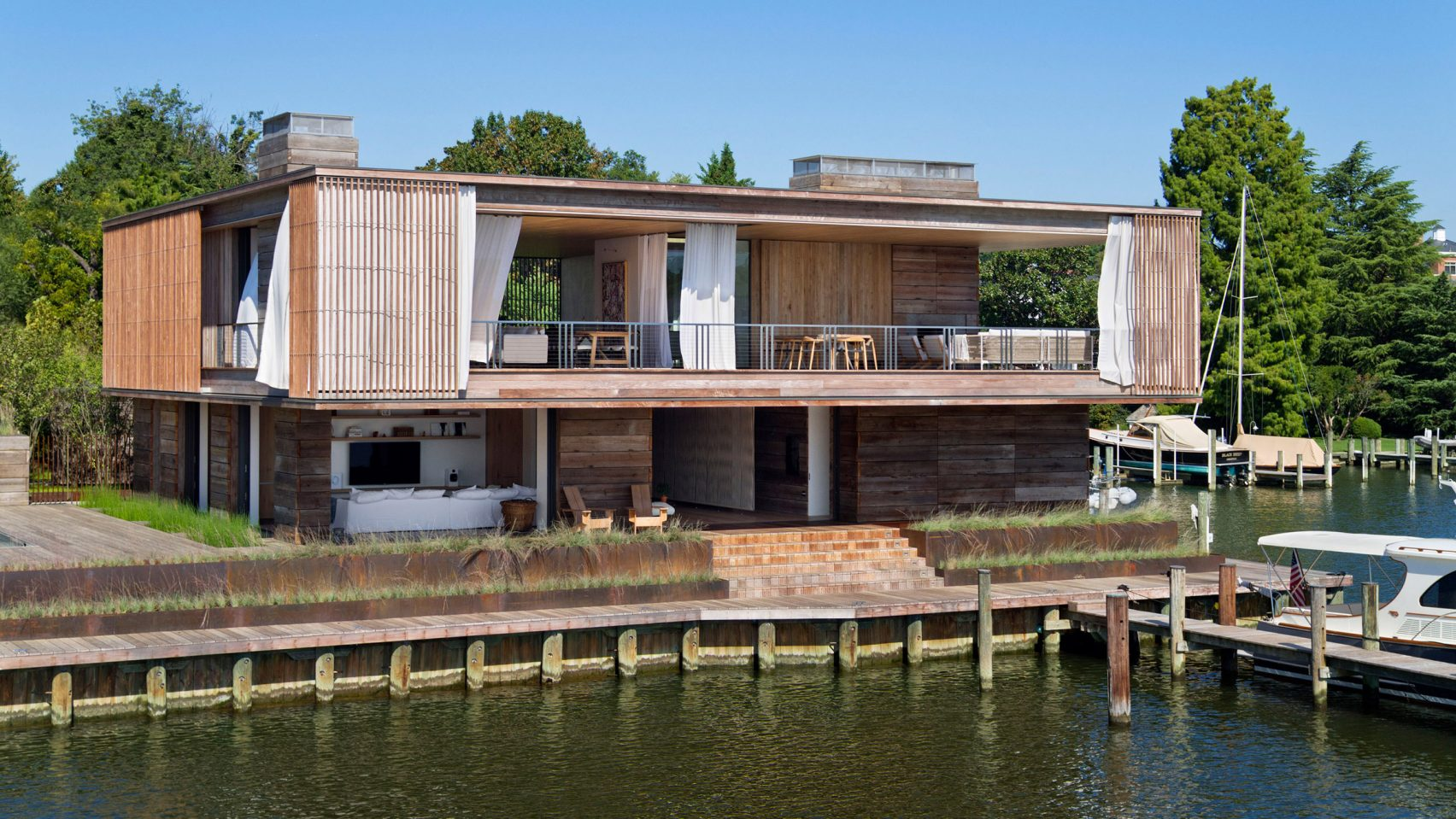 Bates Masi, wooden home, sailing family, Annapolis, waterfront, New York, Chesapeake Bay, Acton Cove, Maryland, capital city, Us Naval Academy, dock, boat, residence, boating, sliding glass door, curtain, indoor, outdoor, privacy, weather, living room, cantilevered decks, balcony, Acton Cove, modern, nautical aesthetic, white walls, cabinet, furniture, kitchen, couch, six PP503 chair, Hans J Wegner, swimming pool, dock, pool, bedroom, en-suite bathroom, Acton House, garage, studio, garden, Virginia-based Gregg Bleam